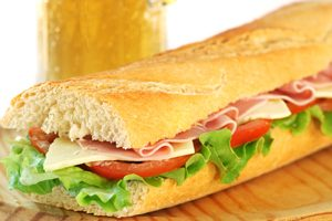 baguette sandwich with lettuce, tomatoes, ham, and cheese with a glass of beer in the background